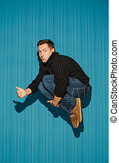 Portrait of young man with serious facial expression jumping...