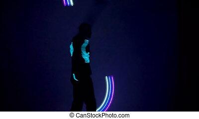 Man twist fiery figures on a light show.