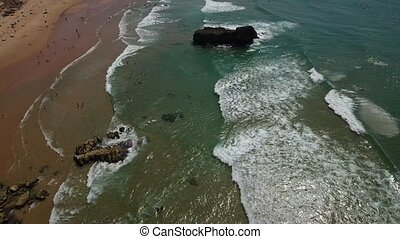 Aerial. Tonel flight over the beach, with the waves and...