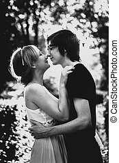 black and white photo of guy  the girl embracing on a background  park alley
