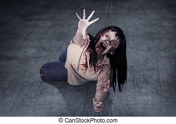 Female zombie crouching on the floor. Halloween concept