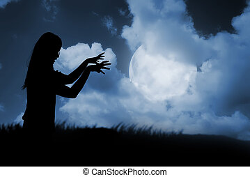 Silhouette of woman zombie walking under full moon....