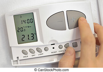 pressing button on digital thermostat - hand pressing button...
