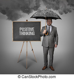 positive thinking text on blackboard with businessman...