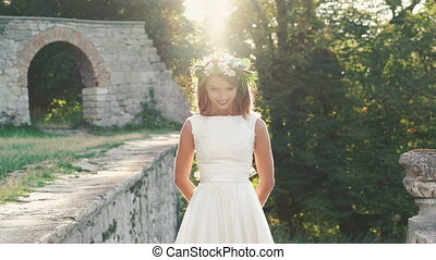 Pretty bride in gown raises her head and smiling to the...
