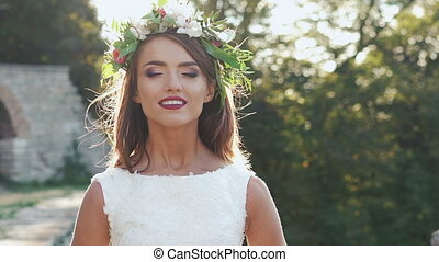 Pretty girl in wreath looking on a camera. Slowly