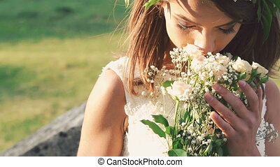 Close up of bride smelling bouquet, smiling and looking on...