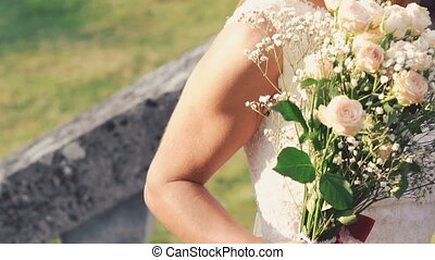 The bride smelling bouquet, smiling and looking on sun....