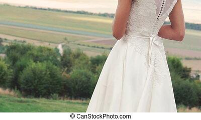 Cute bride standing in the windy fields. Slowly.