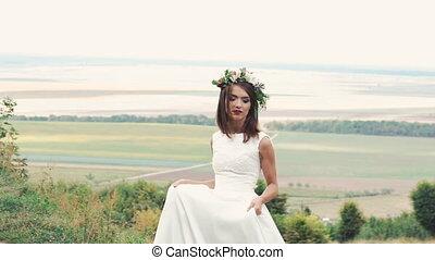 Happy bride walking in gown in the field. Slowly.