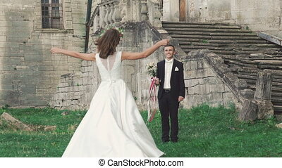 Smart bride running to the groom standing with bouquet. Slowly