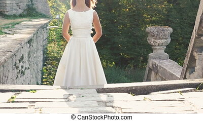 Silhouette of pretty bride in gown standing under the sun on...
