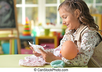 Girl playing with baby doll - Portrait of cute little girl...