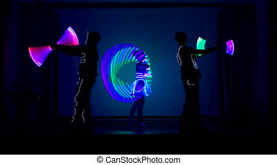 Two men and a woman performes light show. - Two men and a...