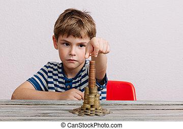 Boy building stack of cash