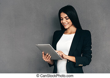 Examining her new tablet. Attractive young woman in smart...