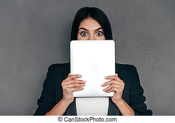 Tablet needs to be fixed? Surprised young woman holding digital tablet and looking out of it while standing against grey background