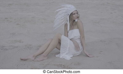 Woman with white feather indian hat at the beach - Blond...