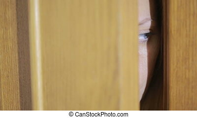 girl spies through a door crack. Eye looking through a slit...