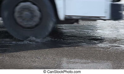 A puddle of water on the road - Puddle with potholes on the...
