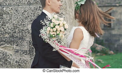Cute wedding couple caressing and kissing near the brick wall. Slowly