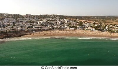 Aerial. Capture video of Luz beach in summer, full of...