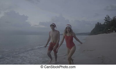 Couple wearing santa hat at the beach - Christmas happy...