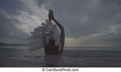 Woman with white feather indian hat at the beach - Back view...