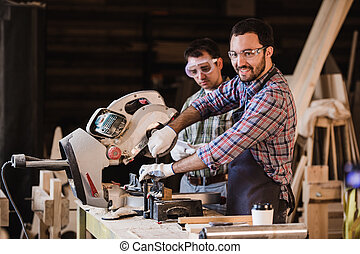 Two carpenters cutting wooden plank with a circular saw -...