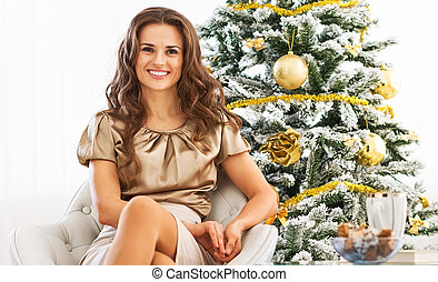 Full length portrait of happy young woman sitting near...