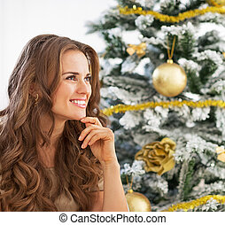 Portrait of thoughtful young woman sitting near christmas...