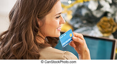 Portrait of thoughtful young woman with credit card and...