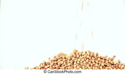 Falling buckwheat on a white background fills the screen. -...