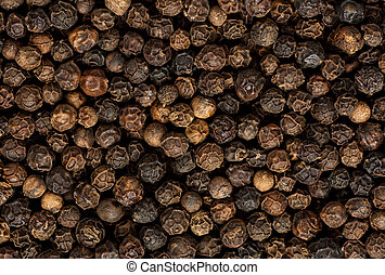 Black pepper grains as background close up.