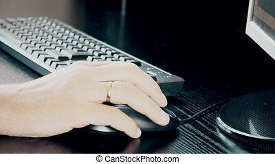 Male hand holding computer mouse with laptop keyboard in the...