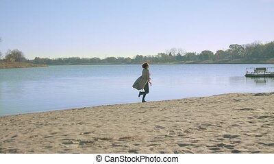 Woman starts running on the shore of the lake. Red leaf.