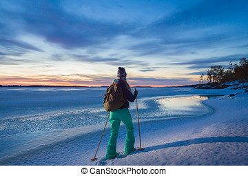 Woman snowshoeing by the lakeside - Young beautiful woman...