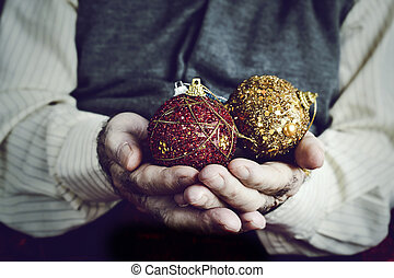 old man with christmas balls in his hands - closeup of an...