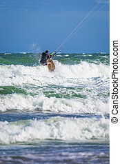 Wan riding kite surf on sea waves - Athletic man riding on...