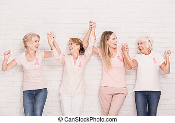 Positive cancer survivors wearing pink, holding each other...
