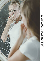 Woman covering her mouth - Broken mirror reflection of...