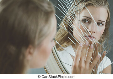 Woman touching broken mirror - Beautiful woman with mental...