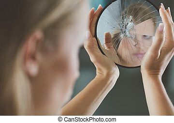 Woman holding small broken mirror - Woman with mental...