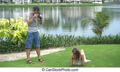 Beautiful model posing for male photographer during outdoor...