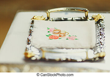 Wedding rings lie on a silver tray