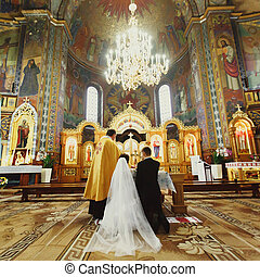 A view from behind on a wedding couple standing on the knees before an altar in church