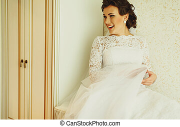 Smiling bride sits behind a white wardrobe