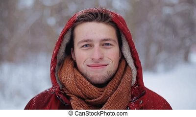 happy man in winter jacket with hood outdoors - people,...