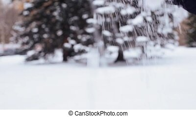 hand pouring snow in winter forest - people, season,...