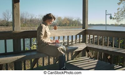 Woman sits on the lake and surfs the internet with laptop